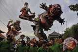 Sejumlah pemuda mengarak Ogoh-Ogoh atau boneka raksasa yang melambangkan Bhuta Kala (sifat-sifat buruk) dalam Festival Ogoh-Ogoh 2014 menjelang Hari Raya Nyepi Tahun Saka 1936 di Desa Tegallalang, Gianyar, Bali, Sabtu (29/3). Umat Hindu menggelar parade Ogoh-Ogoh berkeliling kampung untuk menetralisir kekuatan negatif dan sifat buruk agar Hari Raya Nyepi dapat dilaksanakan dengan penuh keheningan serta tanpa gangguan apapun. ANTARA FOTO/Nyoman Budhiana/nym/2014.