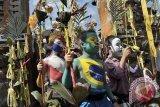 Sejumlah anak dengan riasan tubuh warna-warni dan bendera peserta Piala Dunia 2014, berjalan berkeliling kampung membawa peralatan upacara dalam ritual Grebeg di Desa Tegallalang, Gianyar, Bali, Rabu (25/6). Tradisi ritual berkeliling kampung dengan riasan tubuh warna-warni sebagai cerminan mahluk menyeramkan itu dipercaya sebagai penolak bala dan untuk menciptakan keharmonisan. ANTARA FOTO/Nyoman Budhiana/nym/2014.