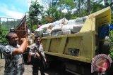 Petugas polisi dan TNI mengamankan lokasi saat memindahkan ribuan bal ganja yang dikemas dalam karung plastik dari mobil interkuler nomor polisi B 9923 HB ke mobil truk lainnya di lintasan Gunung Paro, Kecamatan Leupung, Aceh Besar, Aceh, Rabu (1/10). Mobil truk bermuatan ribuan bal paket ganja sekitar seberat 2,5 ton dalam kondisi rusak itu, awalnya ditemukan petugas polisi hutan yang sedang berpatroli , kemudian dilaporkan e anggota koramil dan polsek tedekat, sementara supir dan pemilik ganja belum berhasil ditangkap. ANTARAACEH.COM/Ampelsa/14