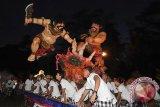 Sejumlah pemuda mengarak Ogoh-Ogoh atau boneka raksasa yang melambangkan sifat-sifat buruk dalam Festival Ogoh-Ogoh 2015 menjelang Hari Raya Nyepi Tahun Saka 1937 di Desa Tegallalang, Gianyar, Bali, Kamis (19/3). Parade Ogoh-Ogoh tersebut untuk menetralisir kekuatan negatif dan sifat buruk sehingga Hari Raya Nyepi dapat dilaksanakan dengan penuh keheningan dan kedamaian. ANTARA FOTO/Nyoman Budhiana/i018/2015.