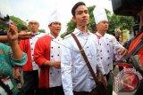 Putra sulung Presiden Joko Widodo, Gibran Rakabuming Raka (dua kanan) bersama sejumlah juru masak berjalan menuju Media Center Jokowi Mantu sebelum memberikan keterangan pers di Sumber, Solo, Jawa Tengah, Selasa (9/6). Dalam kesempatan itu, Gibran memberikan keterangan pers mengenai makanan dan katering yang akan disuguhkan kepada tamu dalam pelaksanaan prosesi pernikahannya pada Kamis (11/6). ANTARA FOTO/Maulana Surya/wdy/15.