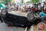Aparat Kepolisian unit lalu lintas Polresta Banda Aceh bersama warga berusah mengevakuasi mobil yang terbalik akibat kecelakaan di jalan Tgk Imum Lueng Bata, Desa Lamseupeng, Banda Aceh, Aceh, Jumat (28/8). Data Badan Kesehatan Dunia (WHO) menyebutkan jumlah kecelakaan lalu lintas di Indonesia yang menyebabkan kematian berada diperingkat ketiga setelah penyakit jantung koroner dan TBC yang diperkirakan sekitar 20-30 ribu orang meninggal akibat kecelakaan di jalan raya. ANTARA FOTO/Irwansyah Putra/pd/15.