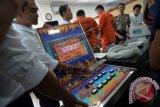 Aparat kepolisian menunjukkan barang bukti mesin judi jackpot dari dua tersangka (ketiga dan keempat kanan) kasus judi saat rilis di Mapolda Jambi, Kamis (17/3). Aparat kepolisian setempat berhasil mengungkap praktik perjudian di sebuah rumah toko dengan keuntungan bersih antara Rp 12 juta sampai Rp25 juta per hari dalam sebuah penggerebekan di kawasan Pasar Jambi dan mengamankan dua tersangka dengan barang bukti beberapa unit mesin judi jackpot dan uang tunai jutaan rupiah. ANTARA FOTO/Wahdi Septiawan/pd/16.