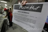 Karyawan Pizza Hut Delivery melakukan aktifitas kerja saat petugas dari Balai Pengawas Obat dan Makanan (BPOM) serta Dinas Kesehatan Kota Surabaya usai melakukan inspeksi  mendadak (Sidak) di Pizza Hut Delivery Jalan Dharmahusada, Surabaya, Jawa Timur, Rabu (7/9). Sidak yang tidak memperkenankan awak media meliput tersebut untuk memeriksa terhadap kemungkinan adanya bahan baku kedaluarsa dalam pembuatan pizza di tempat tersebut. Antara Jatim/Didik Suhartono/zk/16