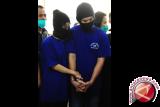 Sepasang kekasih, CL (kiri) dan CF (kanan) yang menjadi tersangka pelaku penyelundupan narkoba berpelukan saat mengikuti rilis ungkap kasus penangkapan narkoba di Mapolda Kalbar, Senin (31/10). CF (26) dan CL (31) beserta kedua rekannya, SS (34) dan HC (38) ditangkap petugas Bea dan Cukai KPPBC TMP C Entikong dan Dit Resnarkoba Polda Kalbar karena membawa 6,3 kilogram sabu, 2.050 happy five dan ekstasi 21 butir dari Malaysia saat mereka melintas di border PLB Entikong pada Jumat (28/10). ANTARA FOTO/Jessica Helena Wuysang/16
