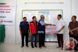 Direktur Utama Telkomsel Ririek Ardiansyah (dua kiri) dan Wakil Bupati Pidie jaya Said Mulyadi (kanan) menyaksikan pengurus PMI Pusat J Dwi Hartanto (dua kanan) menyerahkan bantuan dari pelanggan telkomsel untuk korban gempa kepada pengurus PMI Provinsi Aceh (tengah) di Pidie Jaya, Aceh, Minggu (18/12). Telkomsel menyalurkan bantuan tahap pertama Rp1 miliar itu hasil donasi pelanggan yang dikirim melalui SMS 7788 sejak 8 Desember 2016 melalui lembaga PMI. (ANTARA Aceh/Irwansyah Putra)