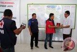 Direktur Utama Telkomsel Ririek Ardiansyah (tiga kiri) menerima plakat terima kasih dari pengurus PMI Pusat J Dwi Hartanto (kanan) seusai menyerahkan bantuan untuk korban gempa dari pelanggan telkomsel di Pidie Jaya, Aceh, Minggu (18/12). Telkomsel menyalurkan bantuan tahap pertama Rp1 miliar itu hasil donasi pelanggan yang dikirim melalui SMS 7788 sejak 8 Desember 2016. (ANTARA Aceh/Irwansyah Putra)