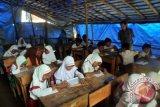 Sejumlah murid mengikuti kegiatan belajar mengajar di SDN Sirna Asih, Kampung Cisarua , Desa Banyuresmi, Kecamatan Cigudeg, Kabupaten Bogor, Jawa Barat. Siswa di sekolah tersebut setiap harinya belajar di kelas yang hanya beratapkan terpal dan berlantai tanah. Para siswa mengharapkan sarana dan prasarana pendidikan yang layak dari pemerintah pusat maupun pemerintah daerah. (ANTARAFOTO/Yulius Satria Wijaya).