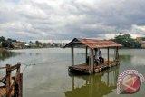 Warga memanfaatkan perahu 'eretan' untuk menyeberangi Situ Citayem yang menghubungkan dua desa diperbatasan Bogor dan Depok, Citayam, Kabupaten Bogor, Jawa Barat, Senin (30/1). Jasa penyeberangan eretan yang menghubungkan dua desa di perbatasan Depok dan Bogor masih bertahan sejak puluhan tahun untuk digunakan oleh warga sekitar untuk mempersingkat jarak dan waktu tempuh dengan ongkos sukarela antara Rp1.000 - Rp. 2.000 untuk sekali penyeberangan. (ANTARAFOTO/Yulius Satria Wijaya).