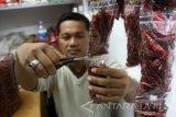 Seorang pedagang melayani pembelian cabai kering impor dalam plastik yang dijual Rp2000 per bungkus di Pasar Dinoyo, Malang, Jawa Timur, Rabu (2/3). Sejumlah pedagang memilih untuk menjual cabai kering dengan harga Rp75 ribu per kilo yang diimpor dari India dan China terkait masih tingginya harga cabai segar yang harganya berkisar Rp100 ribu per kilogram. Antara Jatim/Ari Bowo Sucipto/zk/17