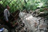 Seorang anggota Polisi memeriksa salah satu rumah yang terkena longsor di Desa Surat, Kecamatan Mojo, Kediri, Jawa Timur, Jumat (7/4). Longsor pasca hujan deras di wilayah lereng gunung Wilis tersebut mengakibatkan enam rumah warga rusak parah. Antara Jatim/Prasetia Fauzani/zk/17