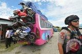 Sejumlah personel kepolisian Polres Palu mengidentifikasi kendaraan bermotor yang diangkut menggunakan bus Antar Kabupaten Dalam Provinsi (AKDP) di Terminal Angkutan Darat Mamboro, Palu, Sulawesi Tengah, Kamis (15/6/2017). Razia sepeda motor yang akan diangkut pulang mudik dengan bus itu untuk memastikan legalitas dan keamanan kendaraan selama perjalanan. (ANTARA FOTO/Basri Marzuki)