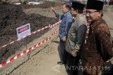 Wakil Presiden Jusuf Kalla (kiri) Gubernur Jawa Timur Soekarwo (tengah) menyaksikan pembangunan mega proyek Sistem Pengelolaan Air Minum (SPAM) Umbulan, di Desa Umbulan, Winongan, Pasuruan, Jawa Timur, Kamis (20/7). Mega proyek SPAM Umbulan bertujuan mengalirkan air curah dengan kapasitas produksi sebesar 4.000 liter air per detik dengan jaringan sistem transmisi dari mata air Umbulan ke lima Perusahaan Daerah Air Minum (PDAM) di Provinsi Jawa Timur, yaitu masing-masing PDAM Surabaya (1.000 liter per detik), PDAM Kabupaten Pasuruan (410 liter per detik), PDAM Kota Pasuruan (110 liter per detik), PDAM Kota Sidoarjo (1.200 liter per detik), dan PDAM Kota Gresik (1.000 per detik).  Antara Jatim/Umarul Faruq/zk/17