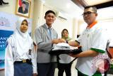 Direktur SDM dan Hukum PT Pelabuhan Indonesia II (Persero)/IPC, Rizal Ariansyah (kanan) secara simbolis menyerahkan atribut kepada siswa berprestasi dari Kalimantan Barat saat pembukaan sekaligus pelepasan Siswa Mengenal Nusantara (SMN) 2017 di Kantor PT Pelabuhan Indonesia II (Persero) Cabang Pontianak, Senin (24/7). Kegiatan SMN 2017 yang diadakan oleh PT Pelindo II (Persero)/IPC bersama PT Perkebunan Nusantara XIII serta diikuti 40 siswa berprestasi dari Kalbar dan Gorontalo tersebut, bertujuan agar siswa dapat saling mengenal keberagaman budaya, kekayaan alam, potensi daerah dan kewirausahaan. ANTARA FOTO/Jessica Helena Wuysang/17