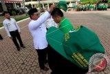 Wakil Bupati Aceh Utara Fauzi Yusuf (kiri) memakaikan topi Kuliah Kerja Nyata (KKN) kepada perwakilan mahasiswa Universitas Malikussaleh (Unimal) pada pelepasan peserta KKN Pemberdayaan Pembelajaran Masyarakat (PPM) Tim I Angkatan XXII tahun 2017 di Halaman Kantor Bupati Aceh Utara, Lhokseumawe, Aceh, Rabu (2/8/2017). Sebanyak 1165 mahasiswa Unimal ditempatkan di 69 desa pedalaman Aceh untuk mendorong Learning Community dan Learning Society dengan tema Persatuan dan Kesatuan Untuk Mewujudkan Pembangunan Desa. (ANTARA FOTO/Rahmad)