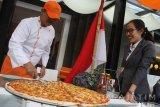 Seorang koki memotong pizza raksasa untuk dibagikan pada pengunjung di Hotel Harris, Malang, Jawa Timur, Senin (14/7). Menu pizza berdiameter 75 centimeter tersebut sengaja dibuat untuk menyambut HUT Kemerdekaan RI sekaligus menarik minat pengunjung. Antara Jatim/Ari Bowo Sucipto/zk/17.