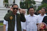 Presiden Joko Widodo (kiri) disaksikan Kepala Staf Kepresidenan Teten Masduki (kedua kiri), Menpora Imam Nahrawi (kedua kanan) dan Menkominfo Rudiantara mencoba kaca mata produk lokal di salah satu stan saat peringatan Hari Sumpah Pemuda ke-89 di Halaman Istana Bogor, Jawa Barat, Sabtu (28/10/2017). Peringatan dengan konsep bernuansa anak muda yang diikuti sekitar 1.000 pemuda berprestasi dari berbagai daerah di Indonesia tersebut mengangkat tema \