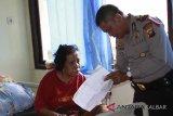 Tenaga Kerja Wanita (TKW) asal Tambaksari Surabaya, Ida Susilawati (kiri) berbincang dengan petugas kepolisian di Puskesmas Entikong, Kabupaten Sanggau, Kalbar, Kamis (8/2). Ida Susilawati (54) yang terserang stroke saat hendak berangkat ke Brunei Darussalam tersebut, telah dirawat di Puskesmas Entikong sejak Kamis (21/12/17) dan hingga kini belum dijemput oleh keluarganya karena keterbatasan biaya. ANTARA FOTO/Agus Alfian/jhw/18