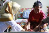 Tenaga Kerja Wanita (TKW) asal Tambaksari Surabaya, Ida Susilawati (kanan) berbincang dengan tenaga medis di Puskesmas Entikong, Kabupaten Sanggau, Kalbar, Kamis (8/2). Ida Susilawati (54) yang terserang stroke saat hendak berangkat ke Brunei Darussalam tersebut, telah dirawat di Puskesmas Entikong sejak Kamis (21/12/17) dan hingga kini belum dijemput oleh keluarganya karena keterbatasan biaya. ANTARA FOTO/Agus Alfian/jhw/18
