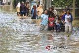 Warga menerobos banjir yang merendam desa Gunungjati, Cirebon, Jawa Barat, Minggu (11/3). Banjir akibat jebolnya tanggul sungai tersebut merendam ratusan rumah warga dan jalur alterntif penghubung Cirebon - Indramayu sehingga mengakibatkan kemacetan. ANTARA JABAR/Dedhez Anggara/agr/18.