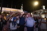 Walikota Liverpool Joe Anderson (ketiga kanan) bersama Wakil Walikota liverpool Gary Millar (tengah) berswafoto dengan latar Hotel Majapahit ketika berburu foto bersama komunitas fotografi di jalur pedesterian Jalan Tunjungan, Surabaya, Jawa Timur, Minggu (18/3).  Kunjungan Walikota bersama Wakil Walikota Liverpool ke Surabaya hingga 22 Maret tersebut bertujuan untuk melanjutkan rencana kerja sama Sister City antara Liverpool dan Surabaya. Antara Jatim/Zabur Karuru/zk/18