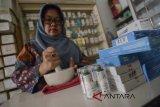 Seorang asisten apoteker meracik obat di Apotek Arcamanik, Bandung, Jawa Barat, Rabu (21/3). Gabungan pengusaha farmasi Indonesia menyatakan pada 2017 industri farmasi, obat kimia dan tradisional tumbuh 6,85 persen, serta investasi di industri tersebut melonjak hingga Rp 5,8 triliun dibandingkan tahun sebelumnya. ANTARA JABAR/Raisan Al Farisi/agr/18