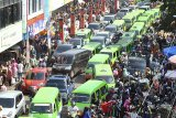 Puluhan angkutan kota terjebak kepadatan lalu lintas di Pasar Dewi Sartika, Kota Bogor, Jawa Barat, Kamis (14/6). Memasuki H-1 Lebaran, sejumlah pasar tradisional dan pusat perbelanjaan di Kota Bogor mulai dipadati warga yang membeli kebutuhan untuk Hari Raya Idul Fitri 1439 H sehingga kemacetan terjadi diruas jalan tersebut. ANTARA JABAR/Arif Firmansyah/agr/18
