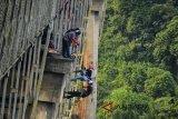 Peserta Pecinta menghabiskan waktu menunggu berbuka puasa (Ngabuburit) dengan mengikuti repling di Jembatan Cirahong peninggalan Belanda, Tasikmalaya, Jawa Barat, Sabtu (2/6). Kegiatan yang diikuti 20 orang peserta yang diselenggarakan oleh touring camp Tasikmalaya dan Pecinta Alam selama bertujuan untuk melawan rasa takut sambil melatih ketangkasan anggota pecinta alam ramadan sambil menghabiskan waktu menunggu berbuka puasa. ANTARA JABAR/Adeng Bustomi/agr/18