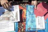 Petugas Kepolisian  menunjukkan sejumlah barang bukti saat gelar perkara Kasus Tindak Pidana Pencucian Uang (TPPU) terkait Miras oplosan Cicalengka di Yayasn SD SMP SMA Bhayangkari, Bandung, Jawa Barat, Kamis (5/7). Kepolisian Jawa Barat menjerat tersangka kasus miras oplosan Samsudin Simbolon dengan  TPPU pasal 3 Undang undang No 8 Tahun 2019 dan menyitas sejumlah aset seperti lima bidang tanah, kebun sawit dan uang sebanyak Rp. 65 juta yang diduga hasil pencucian uang  miras oplosan. ANTARA JABAR/Novrian Arbi/agr/18
