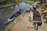 Pekerja memindahkan pasir dari perahu saat melakukan penambangan pasir dari dasar Sungai Citarum di Sapan, Kabupaten Bandung, Jawa Barat, Jumat (27/7). Menyusutnya Sungai Citarum saat musim kemarau dimanfaatkan warga untuk menambang pasir yang mereka jual Rp62.500 per kubik untuk keperluan bahan bangunan. ANTARA JABAR/Raisan Al Farisi/agr/18