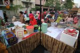 Pengunjung berbelanja makanan di salah satu stan kuliner khas Surabaya saat acara Mlaku-Mlaku Nang Tunjungan atau jalan-jalan ke Tunjungan di Surabaya, Jawa Timur, Sabtu (21/7). Kegiatan yang dimeriahkan dengan berbagai produk UKM dan kuliner khas Surabaya tersebut selain untuk menghidupkan kawasan Tunjungan sebagai salah satu kawasan bersejarah sekaligus untuk meningkatkan perekonomian para pelaku UKM serta mendongkrak jumlah kunjungan wisatawan. Antara Jatim/Moch Asim/18.