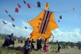 Sekelompok pemuda menerbangkan layang-layang jenis Bebean atau ikan besar dalam Festival Layang-Layang 2018 di Pantai Padanggalak, Denpasar, Minggu (1/7). Festival tahunan selama dua hari tersebut menampilkan sedikitnya 663 layang-layang berukuran raksasa dari berbagai kelompok pemuda di Bali untuk mendukung peningkatan kunjungan wisata di Pulau Dewata. ANTARA FOTO/Wira Suryantala/wdy/2018