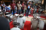 Wali Kota Kediri Abdullah Abu Bakar (kanan) mengamati motor Vespa milik peserta kontes di Gor Jayabaya Kota Kediri, Jawa Timur, Minggu (5/8). Kontes motor Vespa yang terbagi dalam 12 kategori tersebut diikuti sejumlah perwakilan klub vespa se-Indonesia. Antara Jatim/Prasetia Fauzani/zk/18