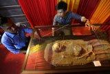 Pengunjung anjungan Pekan Kebudayaan Aceh (PKA) VII Kabupaten Aceh Tengah melihat fosil manusia prasejarah di Taman Sulthanah Sri Ratu Safiatuddin, Banda Aceh, Aceh, Minggu (12/8). Fosil manusia prasejarah tersebut ditemukan dalam goa Ujung Karang yang diperkirakan telah berusia sekitar 7.500 tahun. (ANTARA FOTO/Irwansyah Putra/ama/18)