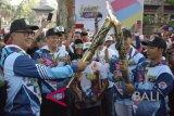 Menteri Sosial Agus Gumiwang Kartasasmita (kiri) menyulutkan api obor yang dibawa atlet Paralimpik cabang atletik I Nyoman Oka (kanan) disaksikan Ketua DPR RI Bambang Soesatyo (kedua kiri) saat Pawai Obor (Torch Relay) Asian Para Games 2018 di Denpasar, Bali, Minggu (16/9). Pawai Obor Asian Para Games 2018 melintasi sejumlah titik di Kota Denpasar sebelum berlanjut ke Kota Pontianak pada Rabu (19/9) mendatang. ANTARA FOTO/Fikri Yusuf/wdy/2018