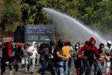 Polisi menyemprotkan air ke pengunjuk rasa dengan meriam air (water cannon) pada simulasi pengamanan Pemilu 2019 di Lapangan Bhayangkara Kompleks Akademi Kepolisian (Akpol) Semarang, Jawa Tengah, Selasa (18/9/2018). Dalam simulasi yang melibatkan sekitar 2.000 personel dari berbagai instansi itu diperagakan berbagai tindakan untuk pengamanan VIP, kampanye, dan penanganan unjuk rasa anarkis. (ANTARA FOTO/R. Rekotomo)