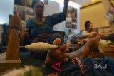 Seorang perajin menunjukkan memilin benang untuk kain tenun khas NTT pada pameran industri kreatif di sela Konferensi Internasional Ekonomi Kreatif di Nusa Dua, Bali, Rabu (7/11/2018). Kegiatan selama tiga hari yang dihadiri sekitar 2.000 peserta dari 30 negara itu merupakan konferensi pertama dan menjadi ajang bertukar ide untuk membangun ekonomi kreatif secara global. Antaranews Bali/Nyoman Budhiana.
