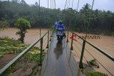 Warga melintasi jembatan gantung di Desa Cipatujah, Kabupaten Tasikmalaya, Jawa Barat, Rabu (7/11/2018). Akibat jembatan Pesangrahan Cipatujah tidak bisa dilalui akibat diterjang banjir bandang, sebagian warga terpaksa melewati jembatan gantung alternatif yang menghubungkan Desa Cipatujah dengan Desa Ciandum untuk beraktivitas meskipun jembatan tersebut tidak layak dilewati. ANTARA JABAR/Adeng Bustomi/agr.