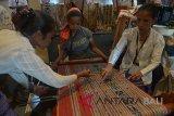 Tiga perajin menujnukkan proses menenun kain khas NTT pada pameran industri kreatif di sela Konferensi Internasional Ekonomi Kreatif di Nusa Dua, Bali, Rabu (7/11/2018). Kegiatan selama tiga hari yang dihadiri sekitar 2.000 peserta dari 30 negara itu merupakan konferensi pertama dan menjadi ajang bertukar ide untuk membangun ekonomi kreatif secara global. Antaranews Bali/Nyoman Budhiana.