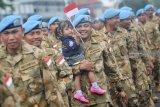 Seorang prajurit TNI AL yang tergabung dalam Satgas Maritim Task Force (MTF) Konga XXVIII.J UNIFIL menggendong anaknya ketika tiba di Dermaga Ujung Koarmada II Surabaya, Jawa Timur, Kamis (8/11/2018). Satgas yang dipimpin oleh Komandan KRI Usman Harun-359 Kolonel Laut (P) Alan Dahlan tersebut kembali dalam jajaran Koarmada II usai mengemban misi perdamaian dunia selama setahun. Antara Jatim/M Risyal Hidayat/ZK