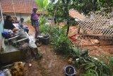 Warga menyaksikan rumah yang tertimbun material tanah longsor di Desa Bojongsari, Kabupaten Tasikmalaya, Jawa Barat, Kamis (8/11/2018). Curah hujan yang tinggi di daerah Tasikmalaya Selatan mengakibatkan sembilan rumah tertimbun tanah longsor dan sebanyak 2.045 jiwa terdampak bencana longsor serta banjir dari 10 Desa yang ada di Kabupaten Tasikmalaya. ANTARA JABAR/Adeng Bustomi/agr.