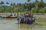 Warga menggunakan kendaraan bermotor menyebrangi sungai menggunakan perahu di Sungai Muara Cipatujah, Kabupaten Tasikmalaya, Jawa Barat, Kamis (13/12/2018). Akibat Jembatan Pansel Cipatujah ambruk diterjang banjir bandang atau pembangunan jembatan bailey belum rampung membuat sejumlah warga beraktifitas menggunakan jasa penyebrangan sungai menggunakan perahu nelayan dengan tarif penyerbrangan sekitar Rp 5.000 hingga Rp 10.000 sekali per motor. ANTARA JABAR/Adeng Bustomi/agr.