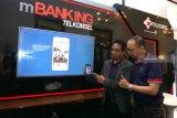 General Manager Digital Banking Telkomsel Rudiyanto Herlambang (kanan) serta General Manager Digital Product Area Expansion Jawa Bali Telkomsel Heribertus Budi Ariyanto (kiri) menunjukkan aplikasi Mobile Banking (mBanking) Telkomsel pada acara peluncuran di Surabaya, Jawa Timur, Selasa (18/12/2018). Aplikasi mBanking Telkomsel akan mendorong terciptanya masyarakat digital Indonesia dengan menghadirkan terobosan baru untuk membangun Indonesia Digital. Aplikasi ini memiliki beberapa fitur menarik, antara lain: transaksi perbankan, transaksi merchant, promo program, sinkronasi data, dan pencari ATM terdekat. Antara Jatim/HO/Ganes A Laksono/ZK.