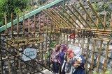 Pengunjung berfoto di salah satu gang di Kampung Labirin, Kebon Jukut, Babakan Pasar, Kota Bogor, Jawa Barat, Minggu (2/12/2018). Kampung Labirin yang menyusuri pemukiman padat dengan gang sempit tersebut menjadi salah satu destinasi wisata baru di Kota Bogor yang menawarkan berbagai menu kuliner tradisional dan potensi kerajinan tangan lokal yang dapat dibuat oleh pengunjung. ANTARA JABAR/Arif Firmansyah/agr.