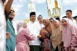 Warga berfoto dengan Presiden Joko Widodo setelah penyerahan sertifikat tanah wakaf kepada pengurus masjid, mushola dan pasantren seusai melaksanakan ibadah Jumat di Banda Aceh, Aceh, Jumat (14/12/2018). Pemerintah telah membagikan lima juta sertifikat tanah termasuk tanah wakaf pada 2016 dan menargetkan tujuh juta sertifikat pada 2018 serta sembilan juta sertifikat tanah pada 2019 mendatang. (ANTARA FOTO/Irwansyah Putra/pd.)