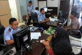 Petugas Imigrasi melayani pemohon saat pembuatan paspor di Kantor Imigrasi Kelas II Meulaboh, Aceh Barat, Aceh, Senin (14/1/2019). Kepala Kantor Imigrasi Kelas II Meulaboh Iman Santoso menyebutkan permintaan pembuatan paspor meningkat sejak Desember 2018 sampai pertengahan Januari 2019 dengan jumlah pemohon mencapai 1.407 pemohon seiring meningkatnya harga jual tiket pesawat jalur penerbangan domestik sehingga sebagian warga memilih menggunakan jalur penerbangan internasional karena harga tiket lebih murah. (Antara Aceh/Syifa Yulinnas)