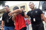 Polisi mengamankan tersangka penyebar hoaks atau berita bohong tujuh kontainer surat suara tercoblos, berinisial MIK (tengah) seusai konferensi pers terkait penangkapan pelaku di Polda Metro Jaya, Jumat (11/1/2019). Ditreskrimsus Polda Metro Jaya menahan seorang guru berinsial MIK dalam kasus tersebut. ANTARA FOTO/Indrianto Eko Suwarso/nym