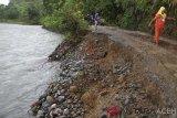 Sejumlah warga melintas di samping jalan lintas antar Desa Jambak dan Desa Sikundo yang tergerus erosi di daerah Desa Jambak, Kecamatan Pante Ceureumen, Aceh Barat, Aceh, Jumat (8/2/2019). Jalan lintas antar desa tersebut terancam putus akibat derasnya aliran sungai apabila tidak segera ditangani oleh pihak terkait. (Antara Aceh/Syifa Yulinnas)