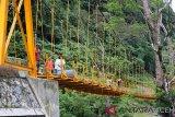 Sejumlah pekerja menyelesaikan pembangunan jembatan gantung yang baru selesai sekitar 95 persen, di Desa Sikundo, Kecamatan Pante Ceureumen, Aceh Barat, Aceh, Jumat (8/2/2019). Pemerintah melalui Dana Otonomi Khusus Aceh (Doka) tahun 2018 membangun jembatan gantung yang menghubungkan Desa Sikundo dan Desa Jambak di Kecamatan setempat sepanjang 90 meter guna membebaskan jembatan tali yang sejak 1979 menjadi sarana penyeberangan warga melintasi sungai Meureubo. (Antara Aceh/Syifa Yulinnas)