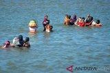 Warga membawa anak menyeberangi muara pelabuhan saat mencari kerang di kawasan pelabuhan perikanan Koetaraja, Banda Aceh, Senin (11/2/2019). Tindakan warga yang mengabaikan keselamatan keluarganya menyeberangi pelabuhan perikanan mencari kerang tersebut, selain untuk konsumsi sendiri juga dijual dengan harga Rp8.000 hingga Rp15.000 perkilogram menurut ukuran kerang tersebut. (Antara Aceh/Ampelsa)